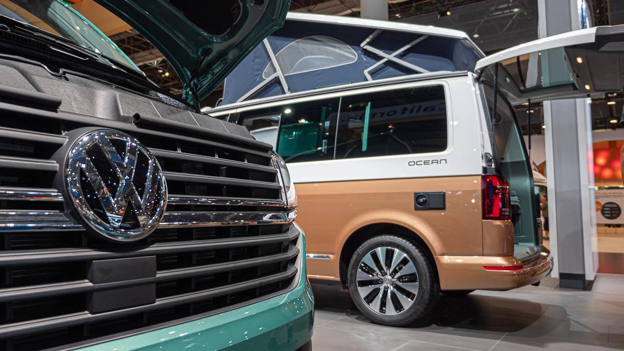 Blick an der Front eines VW California 6.1 Coast vorbei auf das Heck eines VW California 6.1. Ocean mit geöffneter Heckklappe auf dem Messestand des Caravan Salon 2019 in Düsseldorf